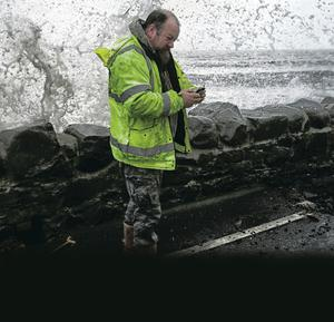 A workman is surrounded by  freezing spray as he assesses the damage to the A2 coastal road at Ballyhalbert.