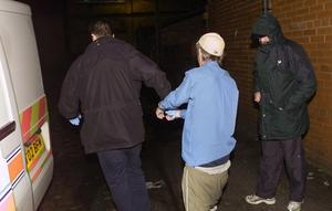 Jonathan Adair being arrested after a raid by police on his home in Bolton in 2003