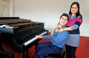 Musical prodigy Rowel Friers at the piano with his mother