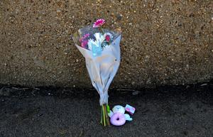 Flowers and a child's toy left near the scene of the crash