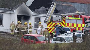 Forensic and fire officers at a house in Derrylin, Fermanagh (Brian Lawless/PA)