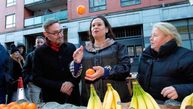 Irish republican Sinn Fein party leader Mary Lou McDonald throws oranges in the air as she talks with a fruit trader (R) during a walkabout in the centre of Dublin, Ireland on February 10, 2020