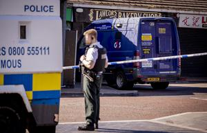 Police at the scene of a cash van robbery at a shop on the Glen Road