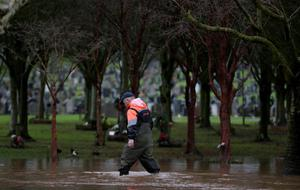 A worker wades through knee-high floodwater at Roselawn cemetery on December 30