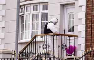 Flowers at front of house as officer collects evidence