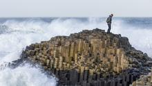 A lone climber on The Honeycomb at Giant's Causeway in Northern Ireland (PA)