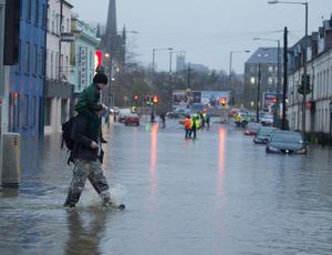 A man carries his son through flood waters in Newry