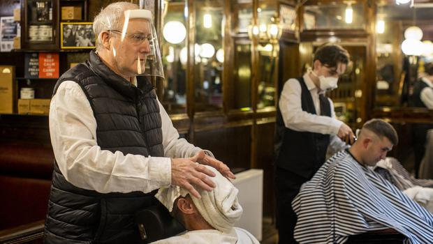 Barbers Michael O'Hare (left) and Stephen Black (right) tending to customers at Cambridge Barbershop on Belfast's Lisburn Road (Liam McBurney/PA)