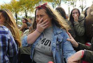 Fans outside the SSE Arena celebrate the news that One Direction would honour their remaining two gigs in Belfast, and that the cancelled one was scheduled for tomorrow night