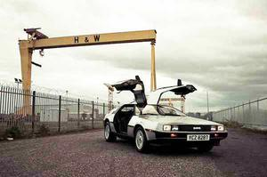 A gull-winged DeLorean car stands in the shadow of one of Belfast's giant cranes