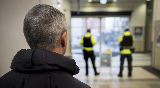 A plain-clothes PSNI officer watches two uniform officers at Belfast Europa Buscentre (Liam McBurney/PA)