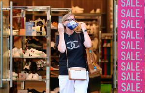 A shopper removes her mask coming out of a shop
