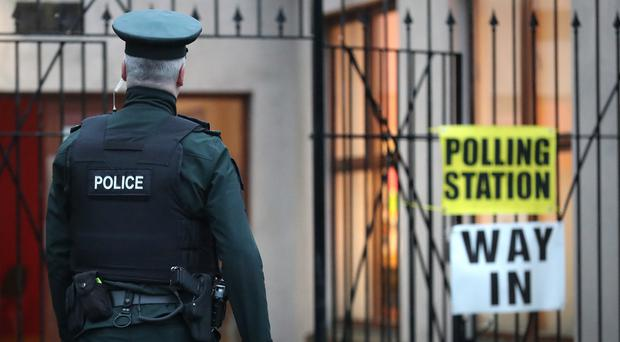 PSNI officers check a polling station at St Peter's Parish Hall in north Belfast, as voters go to the polls in the General Election.