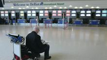 A lone passenger waits in the check-in hall at Belfast International Airport