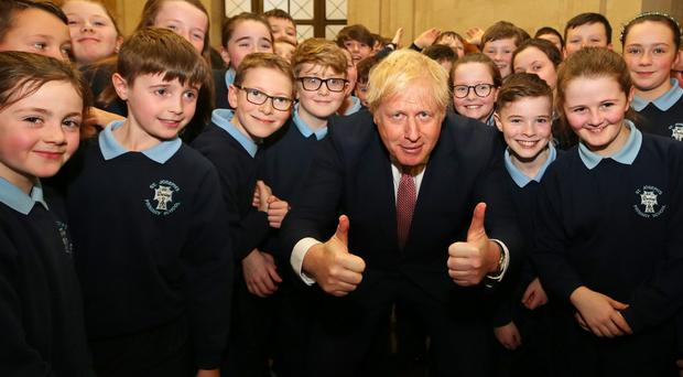 Prime Minister Boris Johnson meets pupils from St Joseph's Primary School, Dunloy in the Senate Chamber at Parliament Buildings