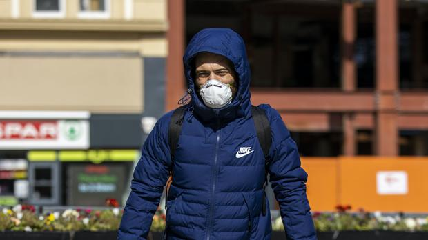 A man wearing a face mask walking through Belfast (Liam McBurney/PA)