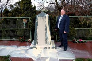 The DUP's Ian McCrea stands beside a memorial to victims of an IRA bomb in Co Tyrone after it was vandalised. Photo credit should read: DUP/PA Wire