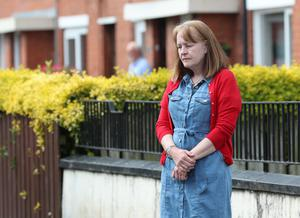 A woman stops on the pavement in Belfast to observe the minute's silence