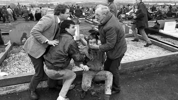 An injured man is aided by mourners, including Sinn Fein vice president Martin McGuinness, left, at Milltown Cemetary (PA)