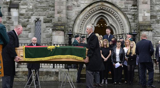 His wife Alison and family members look on as his coffin arrives at the church