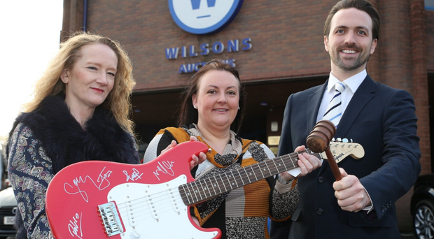 Nicola Flavelle and Michelle Myatt from North Down and Ards Women's Aid hand over the guitar to John Ardill of Wilsons Auctions