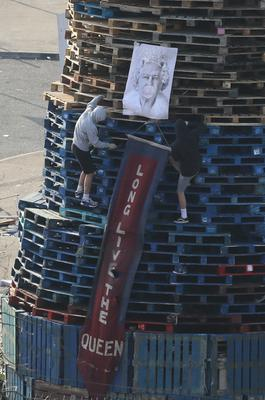 An image of the Queen is added to a bonfire in the Bogside (Brian Lawless/PA)
