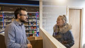 A Belfast pharmacist has built a glass barrier with customers to protect staff from contracting Covid-19 (Liam McBurney/PA)