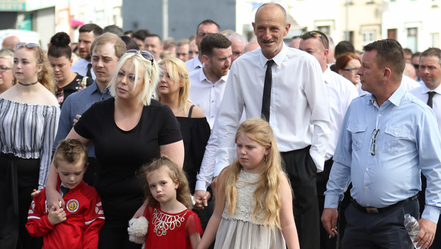 Family members walk behind the coffin of Michael Ginesi as it makes its way to St Peter's Church in Lurgan for his funeral