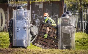 Riot police and contractors remove wood from a bonfire in the Distillery Street area of west Belfast