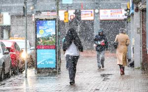 Shoppers and city workers get caught in the snow which fell in Belfast yesterday