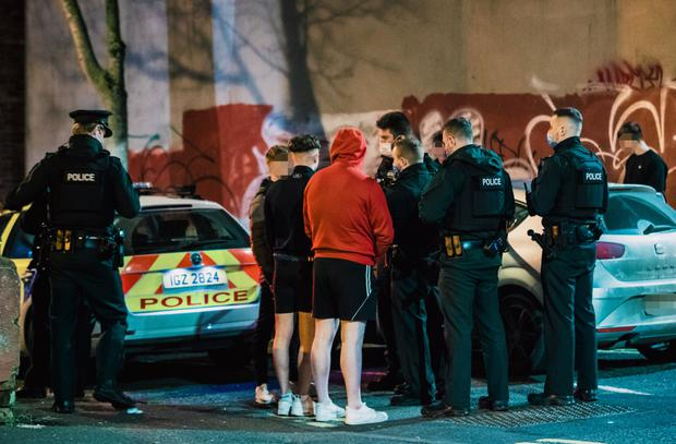 Regulations: Police officers speak to young people in the Holyland area of south Belfast on Monday night