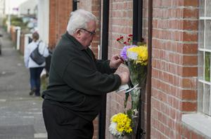 A passer-by leaves a floral tribute near the spot where the bomb went off