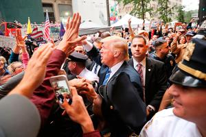 Donald Trump greets supporters outside Trump Towers in Manhattan after facing calls for him to step aside following the emergence of a recording from 2005 revealing lewd comments he had made about Entertainment Tonight presenter Nancy O'Dell