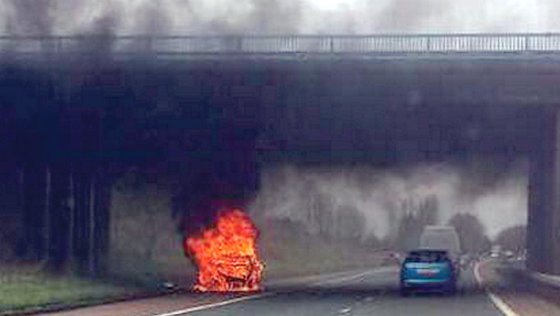 The Smart car ablaze on the side of the M2 near Antrim