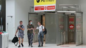 People wear facemasks as they arrive at Belfast City Airport (Brian Lawless/PA)