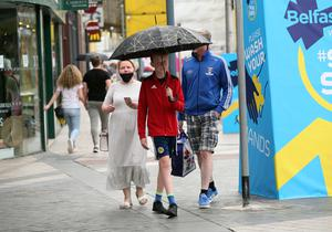 Washout: shoppers in Belfast take cover from the rain last month