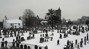 The graveyard at the Church of the Holy Rude in Stirling, the church where James VI was crowned in 1567, is covered in snow