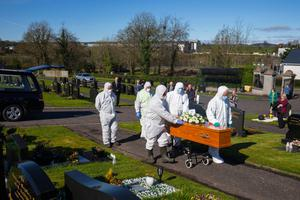 Distancing: Undertakers in protective suits at the funeral of Larry McManus