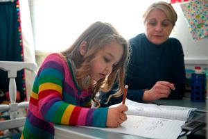 Stressful: A child does her home schooling under the watchful eye of her mother