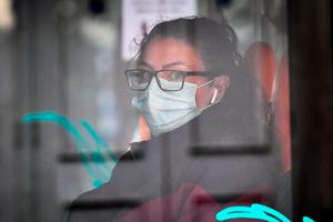 Woman on bus wears a mask