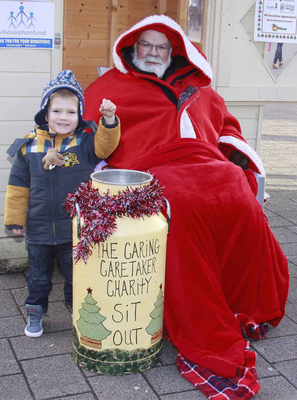 Coleraine's caring caretaker Davy Boyle gets a contribution to his fundraising effort from three-year-old Lucas Orr during his festive sit-out at Coleraine Town Hall