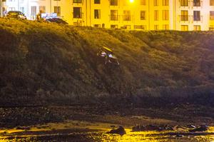 Rescuers at the scene where Shaw's car crashed down an embankment