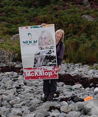 Margaret Anne McKillop with her poster on the beach in Morar on the west coast of Scotland