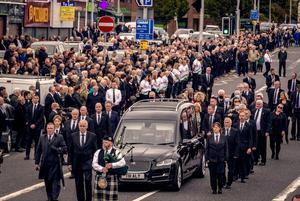 The funeral cortege makes its way to Milltown Cemetery