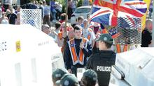 Loyalists hold a white line protest at Twaddell Avenue watched by PSNI officers in August 2013