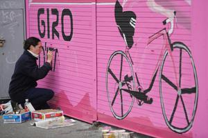 An artist paints a wall in anticipation of the Giro coming to Belfast