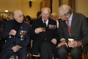 Duke of Abercorn looks at the medals of Arctic convoys veterans William Mahood and John Steen