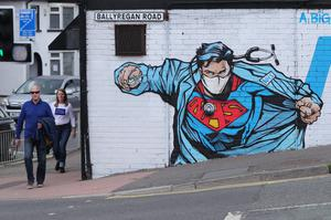 People walk past street art supporting the NHS near to the Ulster Hospital on the outskirts of Belfast (Niall Carson/PA)