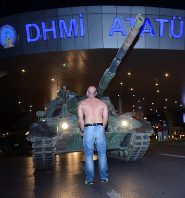 A man stands in front of a tank at the entrance to Istanbul's Ataturk airport