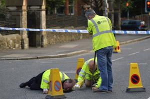 Police and Department of Infrastructure workers at the scene of the sinkhole that forced the closure of the Malone Road yesterday